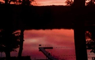 Picture of a dock with a sunset in the background.